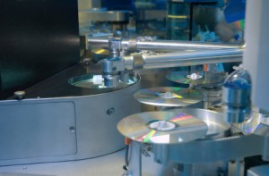 machine making silver cds discs in a factory