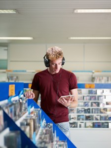 Man with headphone in music shop looking at cds and dvdsImpulse-based selling: a daily routine for packaged media and a challenge for online retailers?
