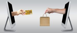 hands coming out of computers with credit card and purchased item in bag, online selling,paying for item sold