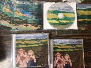 closed cd and an open cd case cd with countryside fields and a farmer and his wife