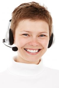 short haired lady ,enormous smile with headset ready to chat