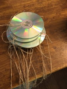 cds with burn side showing ties through centre hole with string