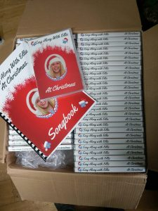 Box of dvds with Christmas theme cover and christmas songbook