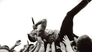 music festival singer being held up by crowds hands